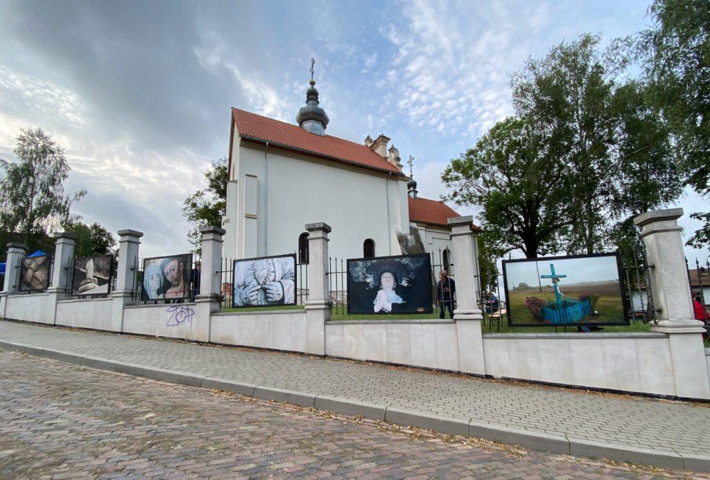 Galeria fotografii Leszka Mądzika na ogrodzeniu szczebrzeszyńskiej cerkwi.